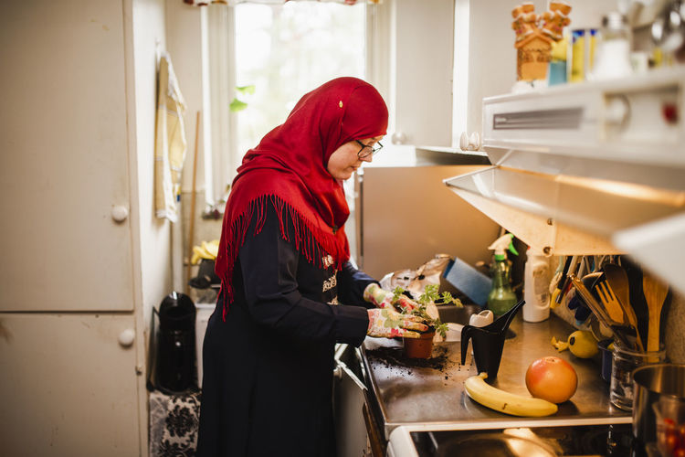 Side view of woman standing by food at home