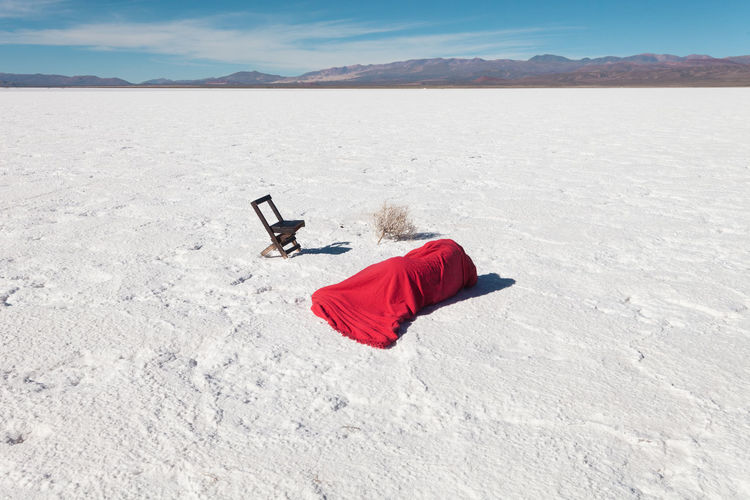 Person wrapped in fabric lying on salt flat