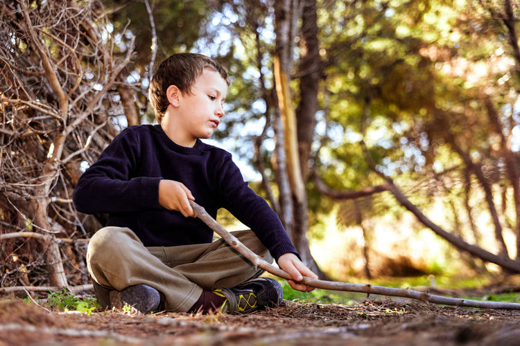 Full length of boy sitting by tree against plants