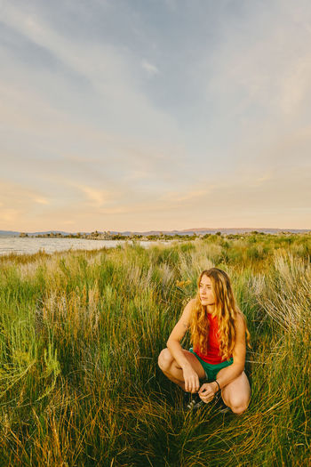 Young woman sitting on grass in field against sky