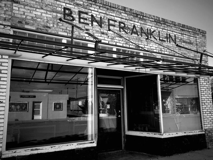 """Reflections of Ben Franklin"" A long defunct Ben Franklin Five and Dime in the historic 12th Street District of Carrizozo, New Mexico, USA. Ben Franklin is a chain of five and dime and arts and crafts stores found in small towns throughout the United States, currently owned by Promotions Unlimited of Mount Pleasant, Wisconsin. The chain originated in Boston in 1877 as Butler Brothers, a mail-order wholesaler selling general and variety-store items. At the turn of the 20th century, Butler Brothers had over 100,000 customers in the United States. As variety stores were penetrating their market, the company founded the Ben Franklin chain in 1927, which was sold in 1959. At Ben Franklin's peak, the chain had 2,500 stores nationwide. Benfranklin Benfranklinstore Historical Building Fiveanddime Blackandwhite Photography Blackandwhite Newmexico NewMexicoTRUE Newmexicophotography Newmexicohistory Roadside America Old Buildings Americanwest"