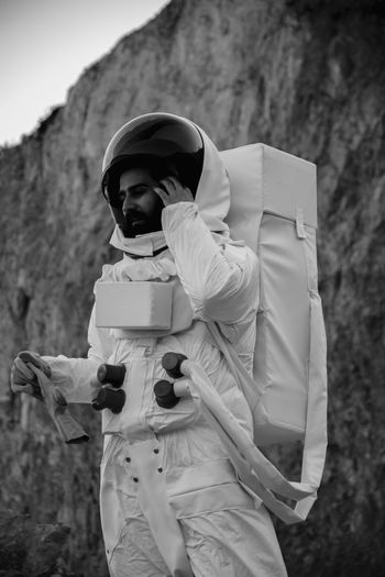 Male astronaut standing against rock formation