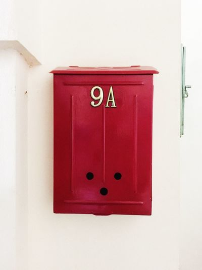 Close-up of red mailbox on wall