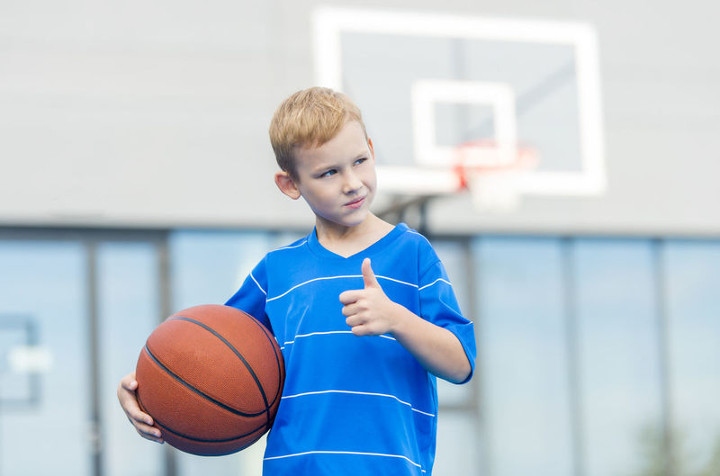 Thoughtful boy gesturing thumbs up while holding ball against basketball hoop