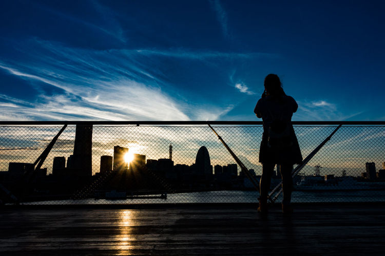 Silhouette of woman standing on bridge over river