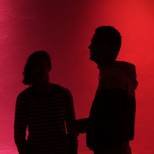 Silhouette man and woman standing against red wall during sunset