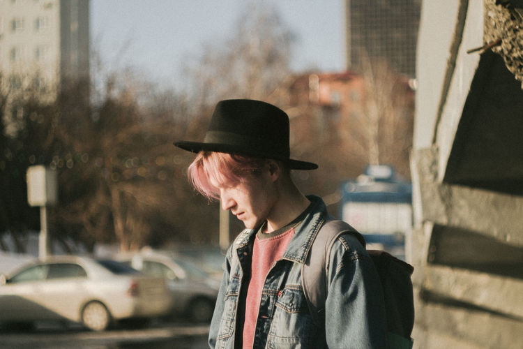 Guy with pink hair stands in the city