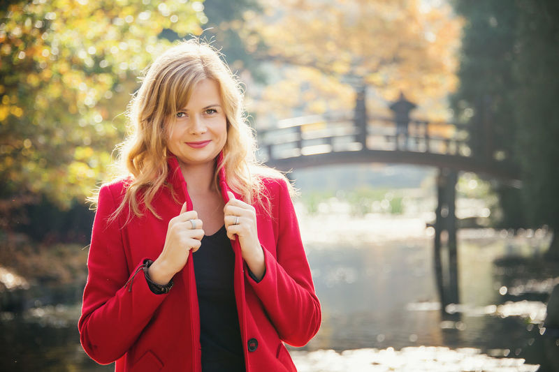 Young attractive woman wearing in red coat in autumn city park