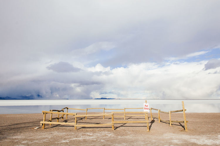 Wooden fence by salt flats against cloudy sky on sunny day