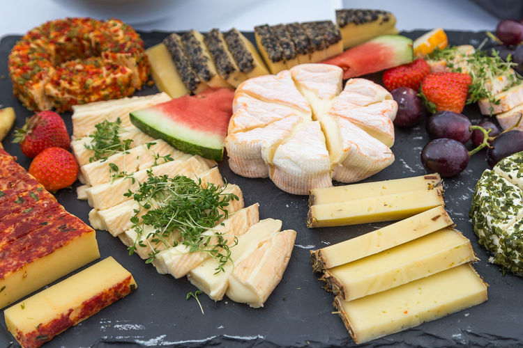 High angle view of various cheese served on stone tray