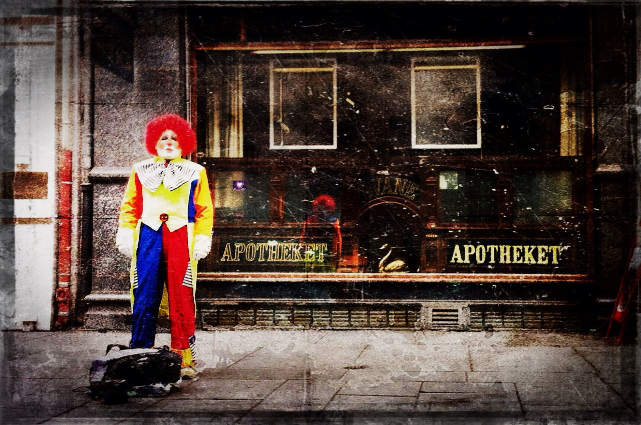 Full length a clown standing in front of a pharmacy store