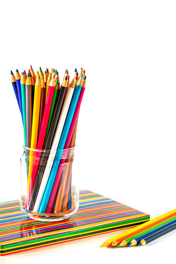 Stack of multi colored pencils against white background