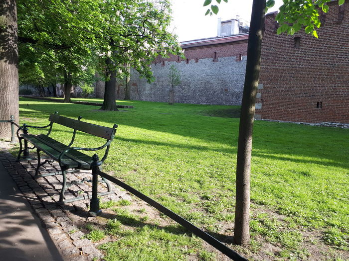 Empty bench on field by building