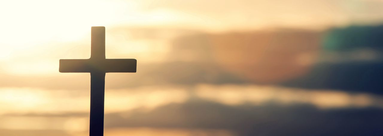 Close-up of cross against sky during sunset