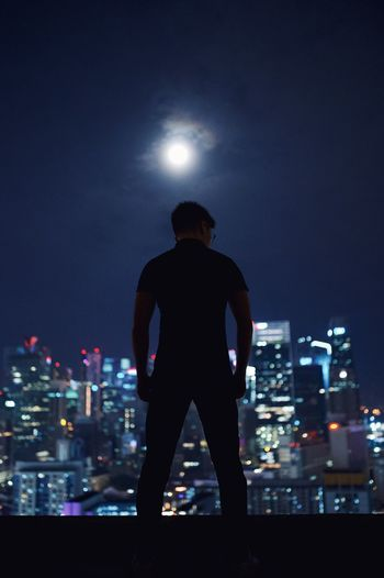 Rear view of silhouette man standing on building terrace against illuminated cityscape at night