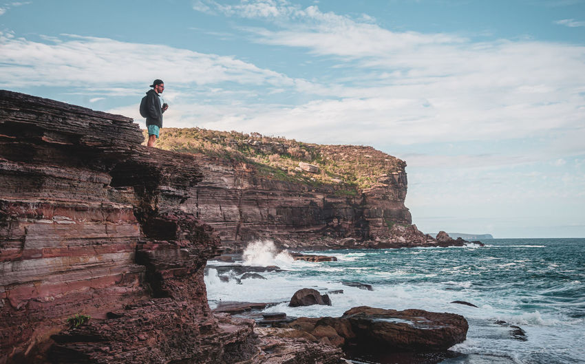Man standing on rock by sea against sky watching the sea