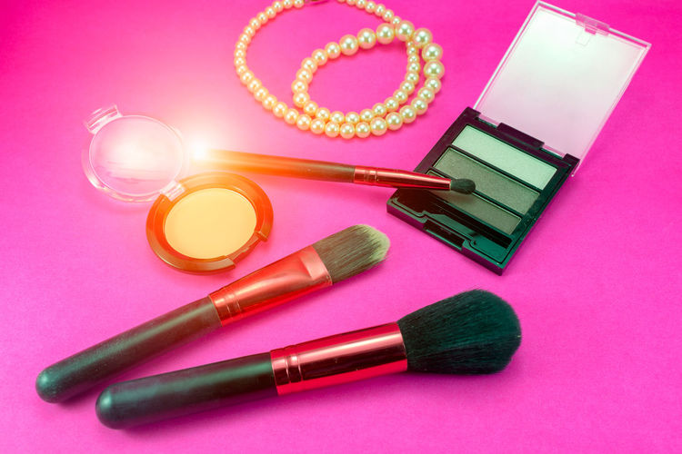 High Angle View Of Make-Up Products On Pink Background