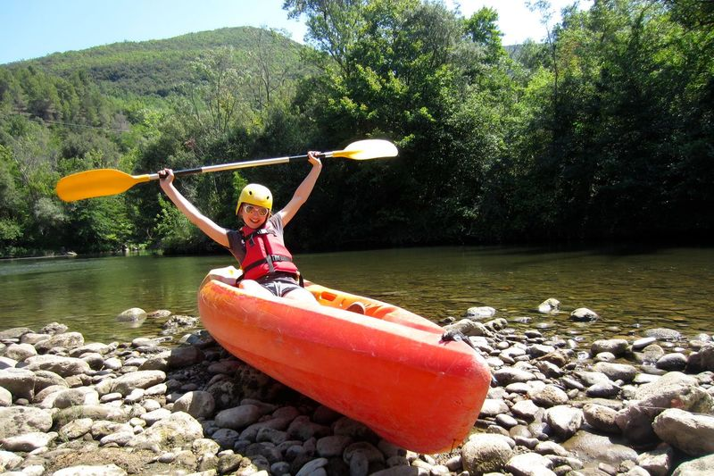 Excited woman holding oar while sitting on kayak at riverbank