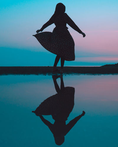 Silhouette Woman At Beach Against Sky At Night