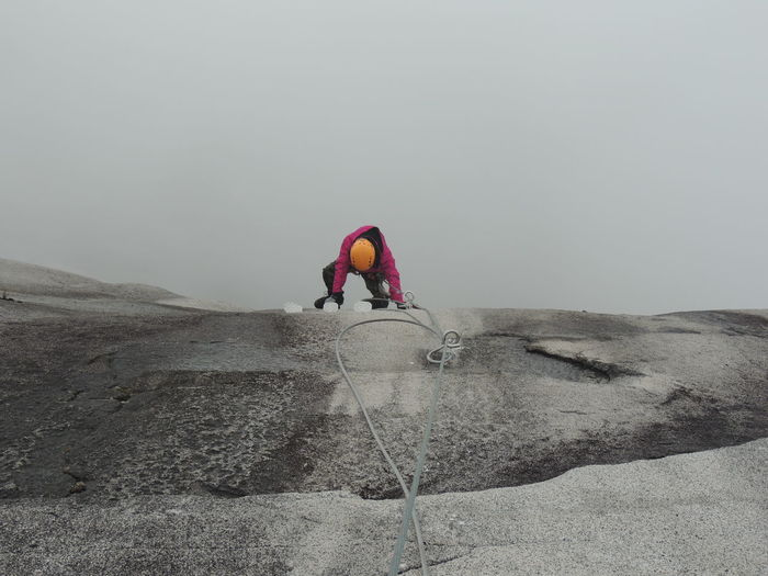Rear View Of Man Climbing On Rock