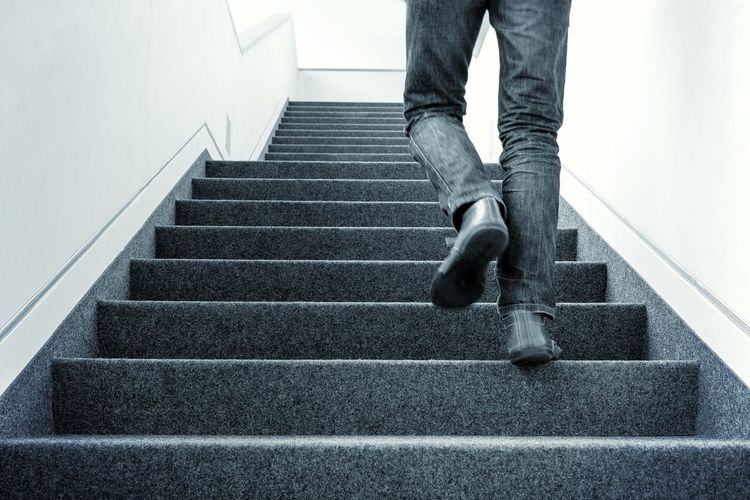 Low Section Of Man Walking On Stairs