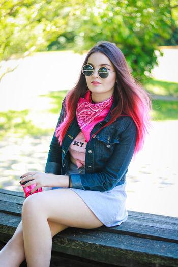 Beautiful young woman sitting at park