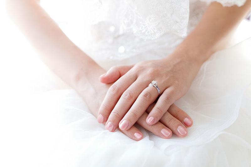 Midsection of bride wearing ring and pink nail polish