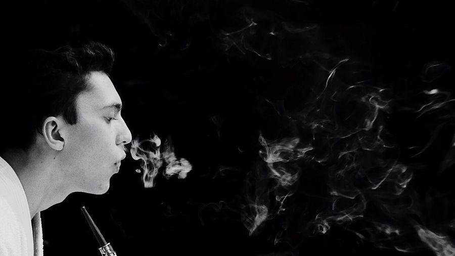 Man smoking hookah against black background