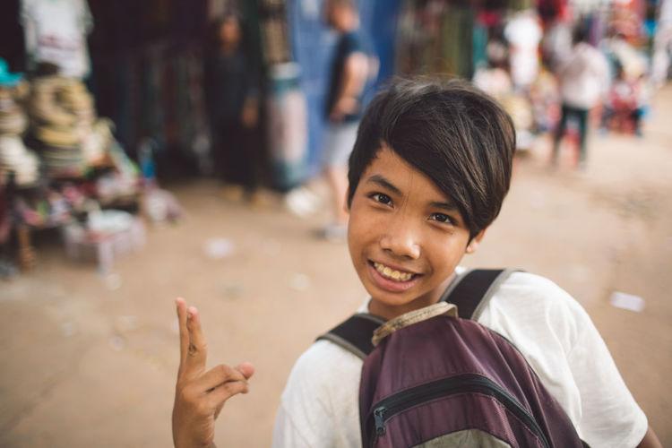 Portrait of smiling boy on street in city