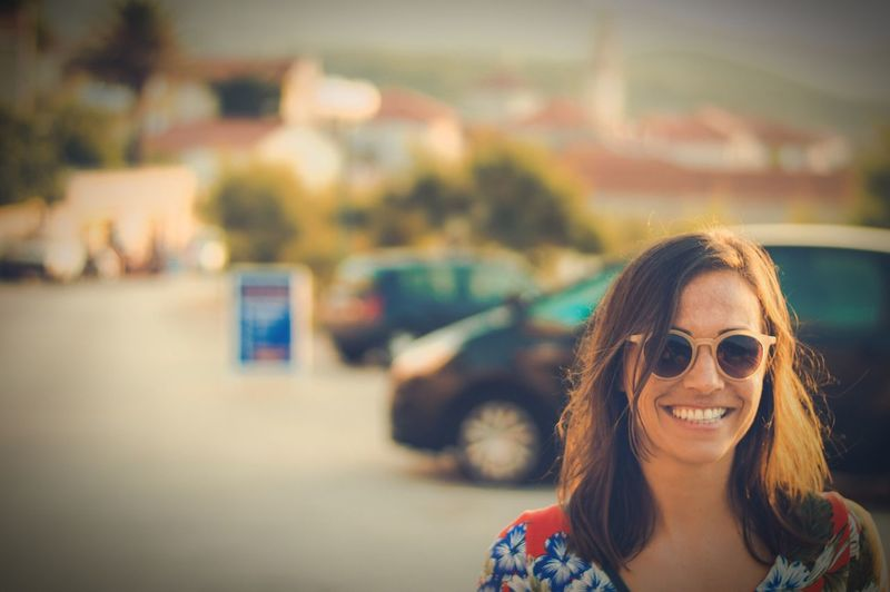 Smiling young woman wearing sunglasses on street