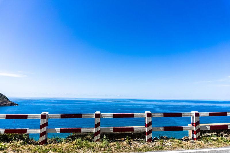 Deck chairs on beach against blue sky