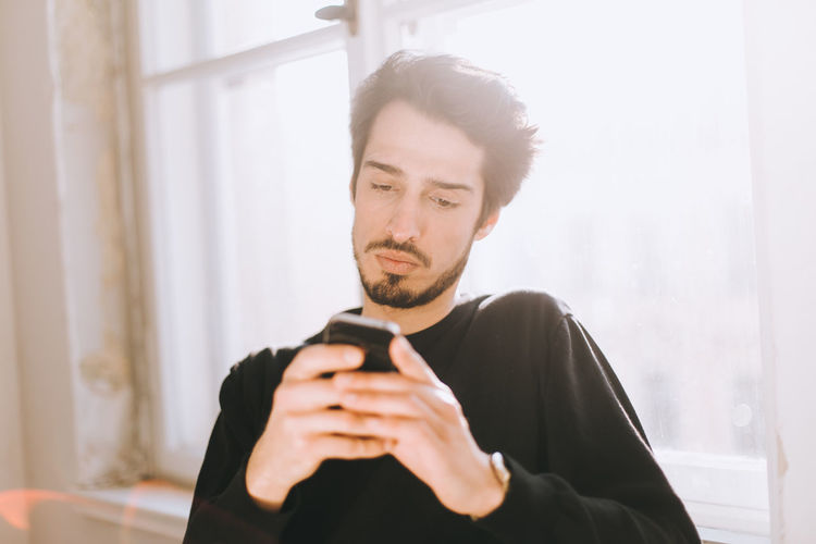 Young Man Using Phone By Window At Home