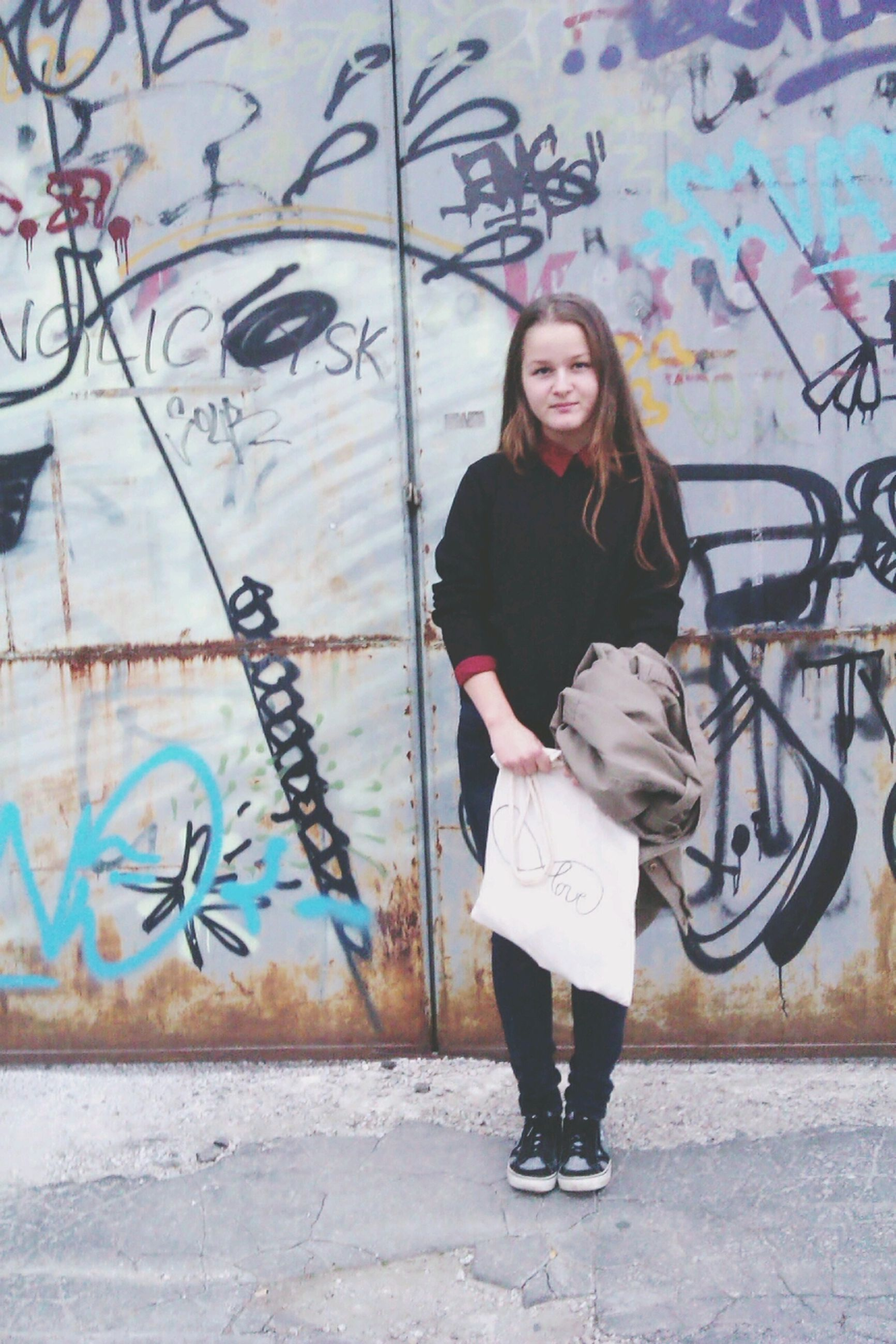 lifestyles, casual clothing, young adult, standing, young women, front view, full length, leisure activity, graffiti, person, looking at camera, wall - building feature, portrait, long hair, built structure, three quarter length, smiling