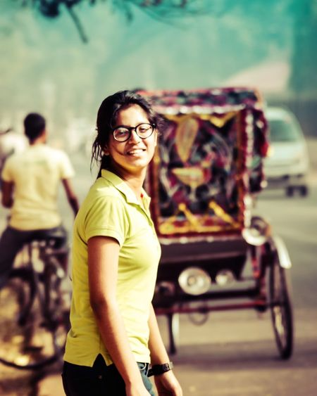 Portrait of teenage girl smiling while standing on road in city