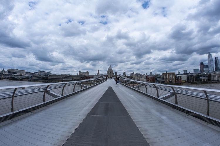 View of footbridge in city against cloudy sky