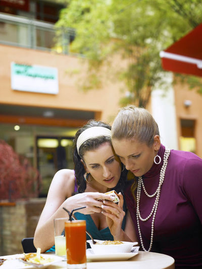 Female Friends Using Phone While Sitting At Outdoor Cafe