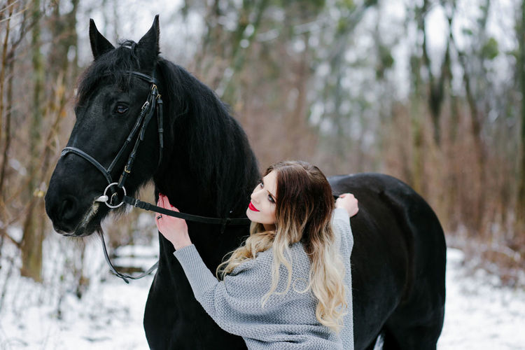 Animal Themes Beauty In Nature Cold Temperature Day Domestic Animals Horse Leisure Activity Lifestyles Mammal Nature One Person Outdoors People Real People Snow Standing Tree Warm Clothing Winter Young Adult Young Women