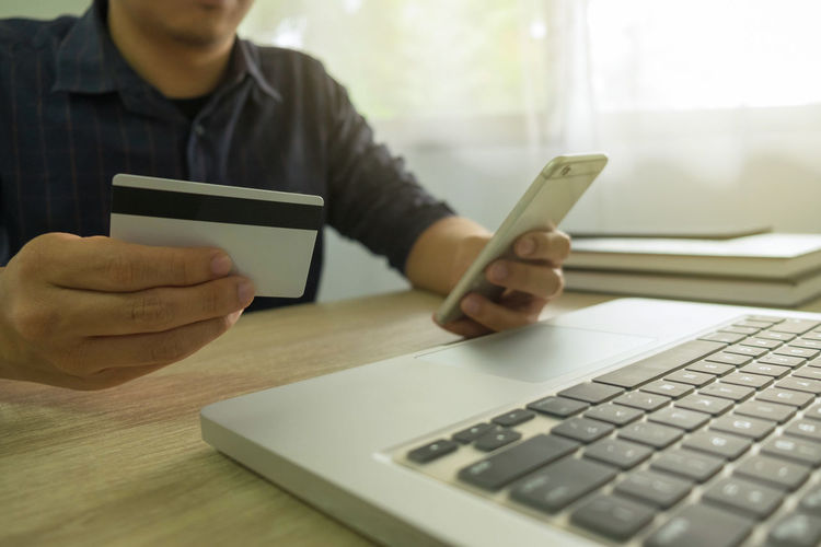 Midsection of man holding credit card while using mobile phone