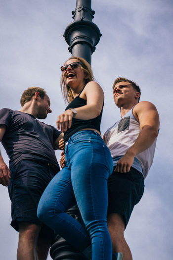 Low angle view of friends against sky