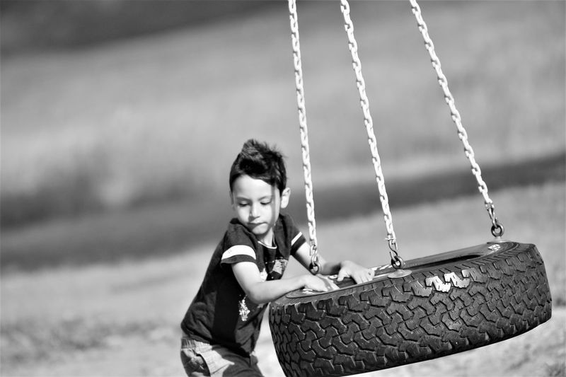 Boy playing with swing at playground