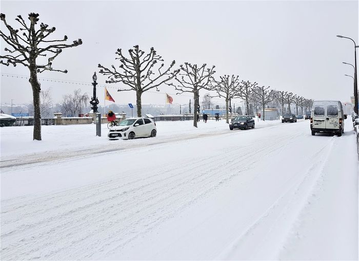 Cars on snow covered road against sky