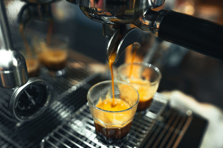 Close-up of drink pouring coffee in glass