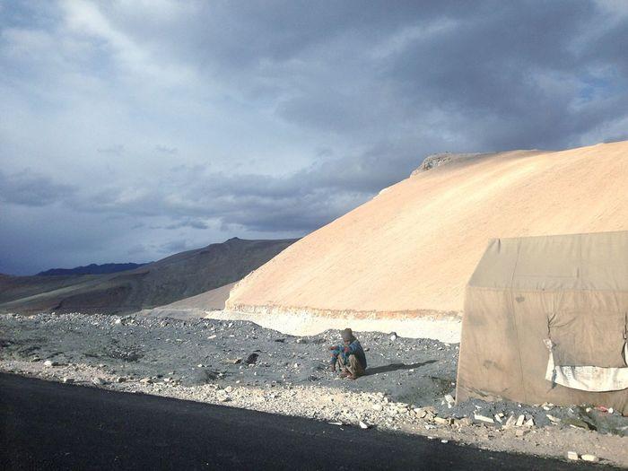 Man Sitting By Tent In Desert