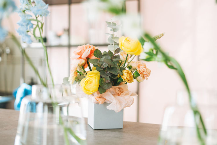 Flower arrangement with yellow and pink roses and eucalyptus in the gift box on table in flower shop