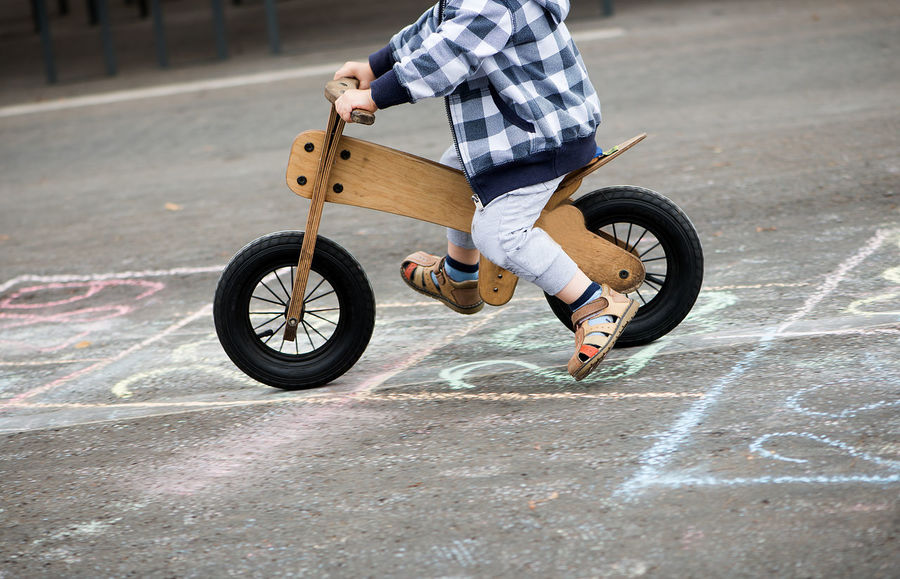 Asphalt Adult Bicycle Child Childhood Day Full Length Hopscotch Human Body Part Human Hand Leisure Activity Lifestyles Low Section Men Motion One Boy Only One Person Outdoors People Real People Riding Stunt Transportation Wooden Bicycle Wooden Bike Fashion Stories