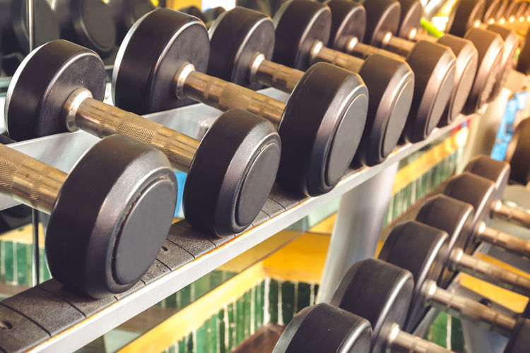 The dumbbell for exercise is arranged neatly in the gym. Fitness Fit Focus Heavy LBS Lifestyle Lift Metal Strong Exercise Iron Close-up Club Dumbbells Equipment Gym Health Healthy Indoors  Kilograms Large Group Of Objects No People Old Storage Weight