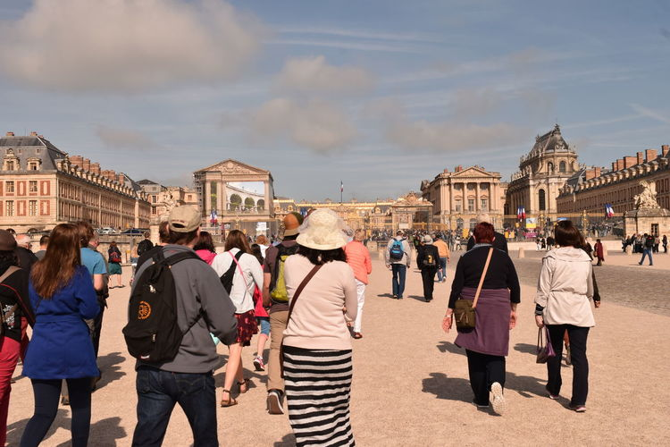 Rear View Of Tourists Walking Towards Chateau De Versailles
