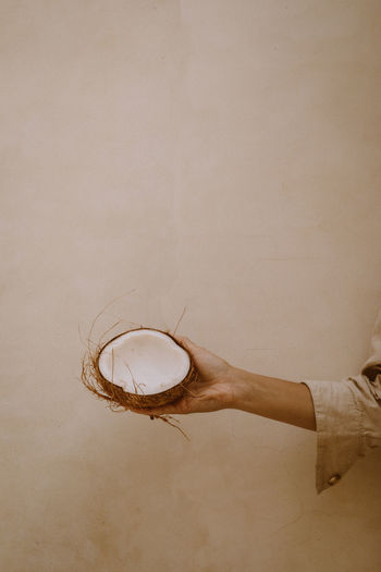 Person holding ice cream against wall