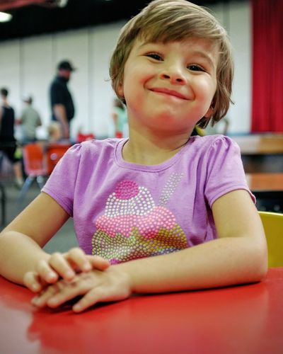 Portrait Of Smiling Girl Sitting At Table In School