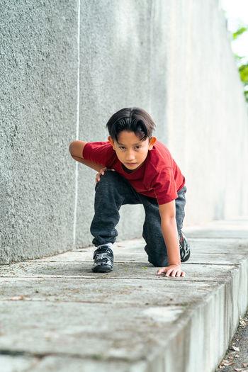 Full length portrait of boy kneeling on footpath